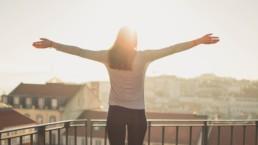 Jente med genser på en balkong vendt mot solen